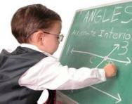 Child genius doing maths at blackboard