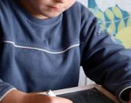 Boy writing maths on blackboard