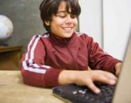 Boy smiling at computer