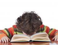 Tired boy reading at desk