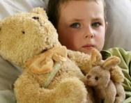 Boy with teddy in bed