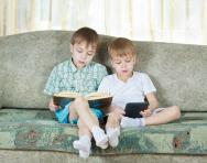 Boys reading printed book and ebook