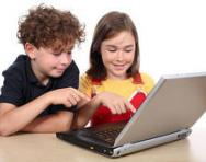 Brother and sister playing on laptop