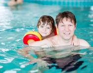 Child and parent in swimming pool