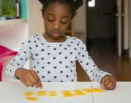 Primary-school maths aids: child counting pasta shapes
