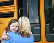 Mum hugging little girl goodbye at school bus