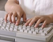 Child typing on a computer keyboard