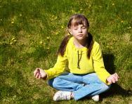 Child meditating in park