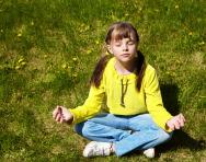 Child meditating in park
