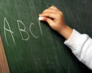 Child writing letters on blackboard