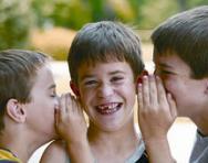 Children whispering in boy's ear