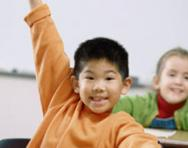 Children putting their hands up in class