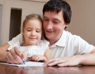 Dad and child writing together