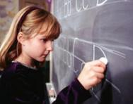 Girl practising writing on blackboard