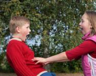 Girl pushing boy playfully