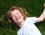 Girl lying on grass laughing