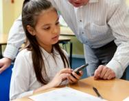 Girl working on maths problem with teacher