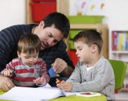 Dad doing homework with child and toddler