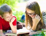 Children reading outdoors