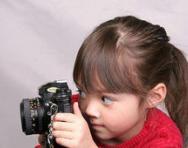 Little girl looking through camera