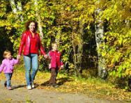 Mum walking with children in woods