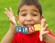Boy holding blocks spelling 'play'