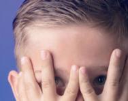 Boy hiding behind his hands
