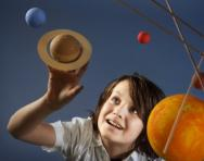 Boy looking at solar system mobile