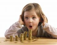 girl looking at pile of coins