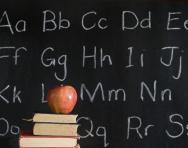 Alphabet on blackboard and apple on book