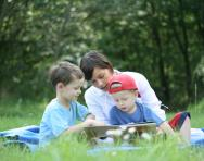 Mother and children reading outdoors
