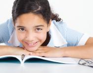 school girl lying on a book
