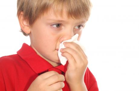 Boy sneezing and wiping nose