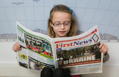 Child reading a newspaper