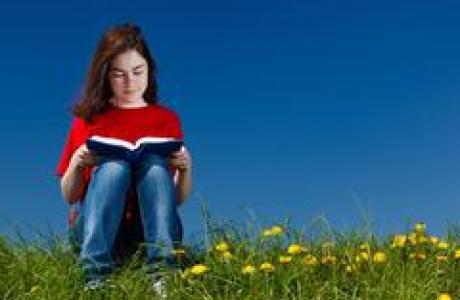Little girl reading outside