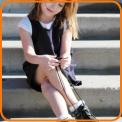 Little school girl tying shoelaces