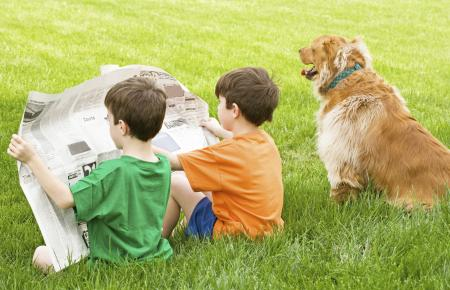 Children reading newspaper