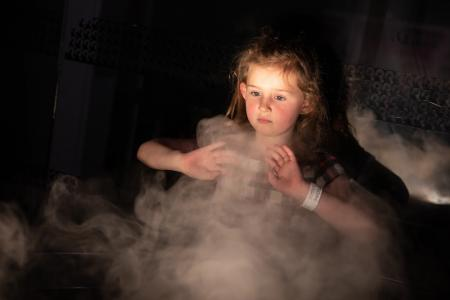 Girl playing with the smoke machine in the dark room at Techniquest